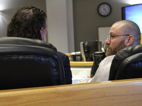 Defense attorney Todd Holmes (L) talks to his client