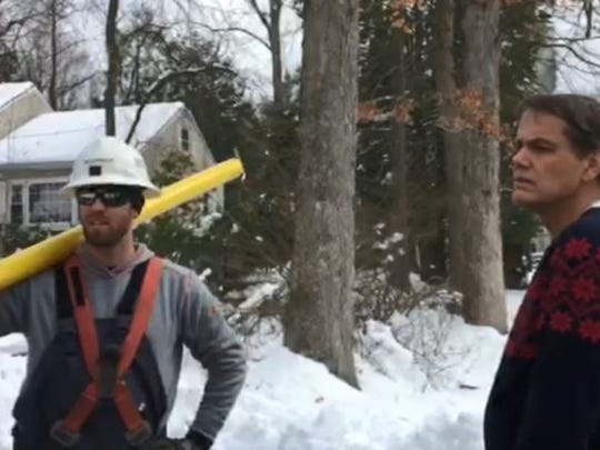 Walter Tennycky, a resident of Braidburn Way in Morris Township listens to a lineman from Potomac Edison restoring the street's power on March 9, 2018.