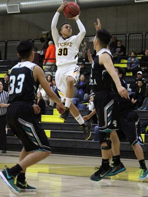Alamogordo's Wellington Balsley, center, puts up a mid-range jumper Tuesday night at the Tiger Pit.