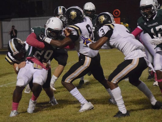 Jena High School defenders Daniel Curry (32, far left), Shaun Todd (8, second from right) and Zyrek Nori (3, far right) wrap up Peabody Magnet High School's Jordan Gaston (29, second from left).