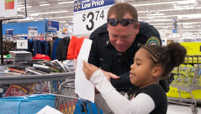 Gallatin Police Sgt. Ritchie helps Aubrey Taylor get everything on her list during Shop with a Cop at Wal-Mart at a previous year's event.