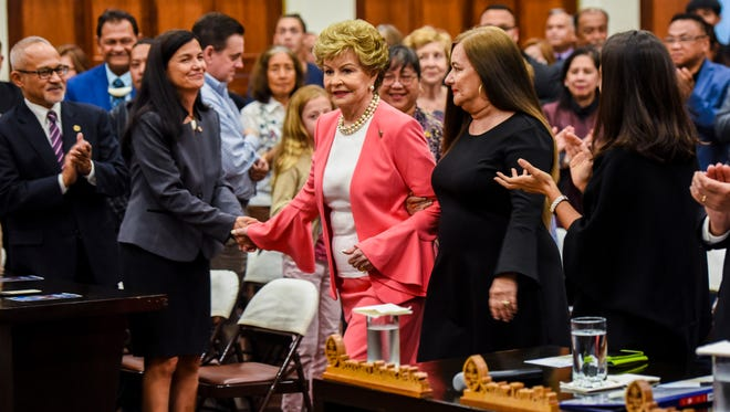 Guam Delegate Madeleine Bordallo, center, is applauded as she enters Guam Congress Building session hall, accompanied by her daughter Deborah Bordallo, on Thursday, Aug. 2, 2018.