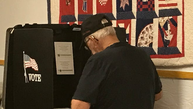 A voter quietly casts his ballot at the American Legion Hall in Shasta Lake.