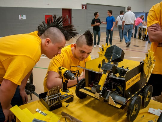 Alamogordo High School seniors Nicholas Baker, left and Angel Baray examine their Terrestrial Invention Gathering Essential Resources or TIGER robot during Saturday's NM BEST Robotics Competition at NMSU's James B. Delamater Activity Center.