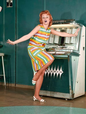 A model dances in front of a jukebox in 1964.