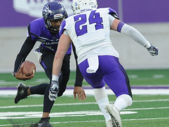 ACU quarterback Sema'J Davis, left, tries to get around