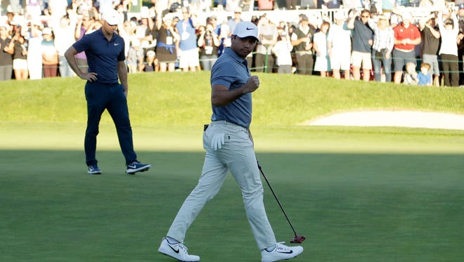 Jason Day, front, reacts after making his putt as Alex Noren looks on during the second playoff hole.
