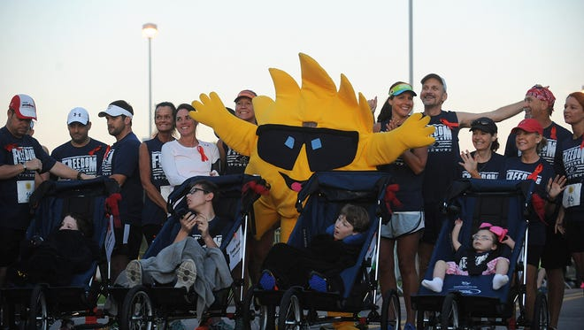 The Rise & Shine Race mascot, Blaze, poses with young wheelchair racers from The Arc of Southeast Mississippi and their partners, the Pine Belt Pacers, at the 2017 Rise & Shine Half-Marathon & 5K on April 1 at Hattiesburg Clinic.