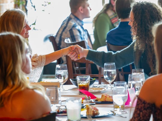 A presenter suggested the students practice a proper handshake during a senior etiquette lunch  at DMACC's Iowa Culinary Institute in Ankeny April 11.