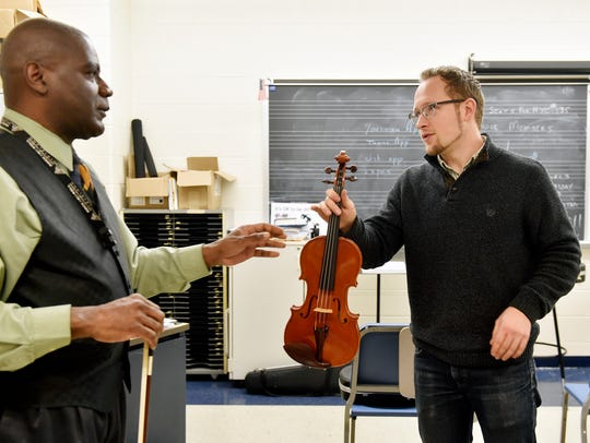 William Penn music teacher Don Carn, left, hands back