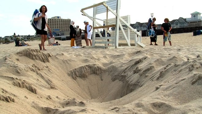 People walk by a hole on the Long Branch beach in 2012. A boy who had been trapped in the hole died of his injuries.