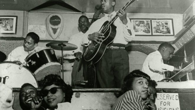 Patrons enjoy a jazz performance at Henri's Cafe Lounge, a club located at 408 Indiana Avenue in Indianapolis owned by Henry Vance. The musicians pictured are Wes Montgomery on guitar, Willis Kirk on drums, Monk Montgomery on bass, and Buddy Montgomery on piano.