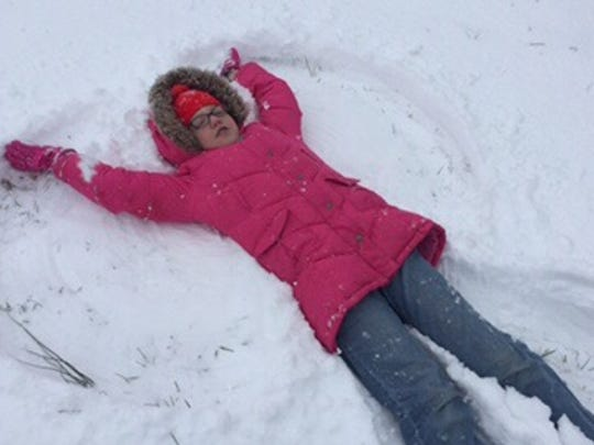 Phoebe Rummel makes a snow angel Friday, Jan. 22, 2016, in her yard on Royal Drive in Wilson County.