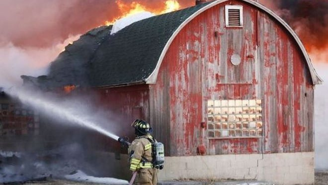 A firefighter battles a blaze in sub-zero temps on this farm near Brandon. The fire in Calumet township is the third fire in Fond du Lac Co. where farm buildings have been destroyed.