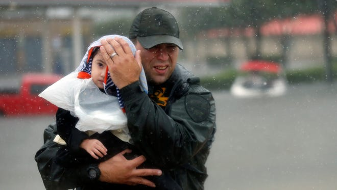 Sgt. Chad Watts of the Louisiana Department of Wildlife and Fisheries holds Madelyn Nguyen, 2, after he rescued her and her family by boat Monday in Houston from floodwaters of Tropical Storm Harvey, which hit Texas last week as a Category 4 hurricane.