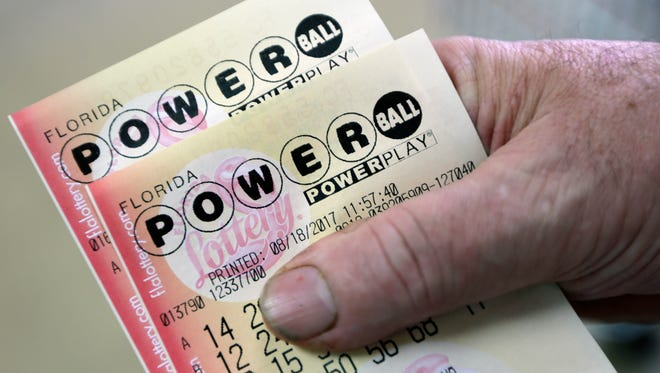 In this Aug. 18, 2017, file photo, a customer shows his purchased Powerball tickets in Hialeah.