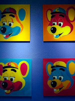"""FILE - This Jan. 16, 2014 file photo shows paintings hanging  on a wall at Chuck E. Cheese's in Dallas. Chuck E. Cheese pizzeria, that Mecca of fun for children but the bane of many parents, is filing for bankruptcy protection. CEC Entertainment Inc. said Thursday, Jan. 25, 2020,  it was filing for voluntary protection under Chapter 11 """"in order to overcome the financial strain resulting from prolonged, COVID-19 related venue closures.â€"""