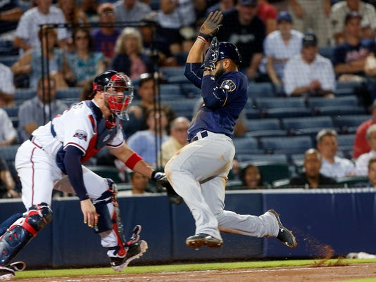 Milwaukee Brewers' Jonathan Villar (5) scores in front of Atlanta Braves catcher Tyler Flowers (25) on a Scooter Gennett base hit in the eighth inning of a baseball game Tuesday, May 24, 2016, in Atlanta. (AP Photo/John Bazemore)