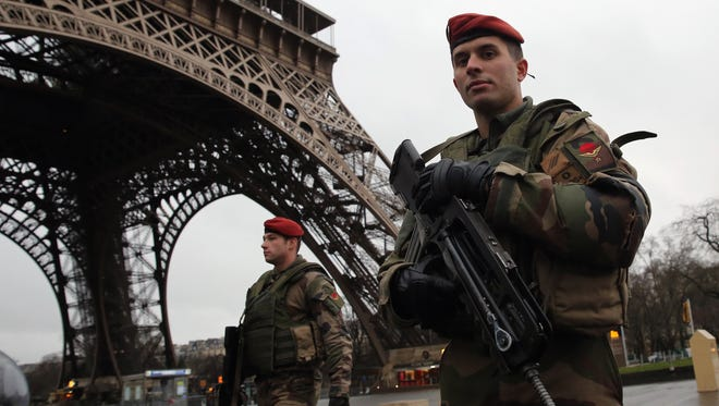 Armed security patrols around the Eiffel Tower on Friday in Paris.