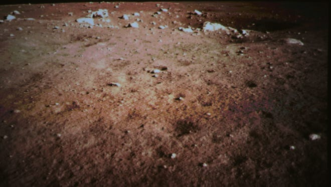 This photo released by China's Xinhua News Agency, shows a picture of the moon surface taken by the on-board camera of the lunar probe Chang'e-3 on the screen of the Beijing Aerospace Control Center in Beijing, capital of China. China on Saturday successfully carried out the world's first soft landing of a space probe on the moon in nearly four decades, the next stage in an ambitious space program that aims to eventually put a Chinese astronaut on the moon.