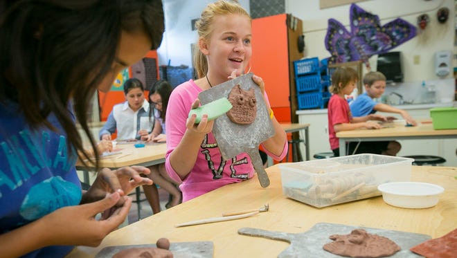 Student Alexis Schwarz, 11, works on a clay sculpture during an art class at Pima Elementary in Scottsdale on Monday, April 21, 2014.