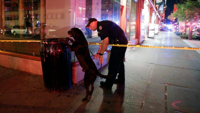 A New York City Police emergency services officer and his dog check a garbage can near the scene of an explosion in Chelsea.