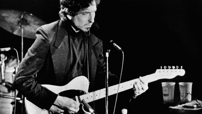 "FILE - In this January 29, 1974 file photo, singer and poet Bob Dylan performs at the Nassau Coliseum, in Uniondale, New York. Dylan was awarded the 2016 Nobel Prize in Literature, one of the most surprising decisions in award's history. The Swedish Academy praised Dylan ""for having created new poetic expressions within the great American song tradition."" This year's winner is set to be announced on Thursday, Oct. 5, 2017."