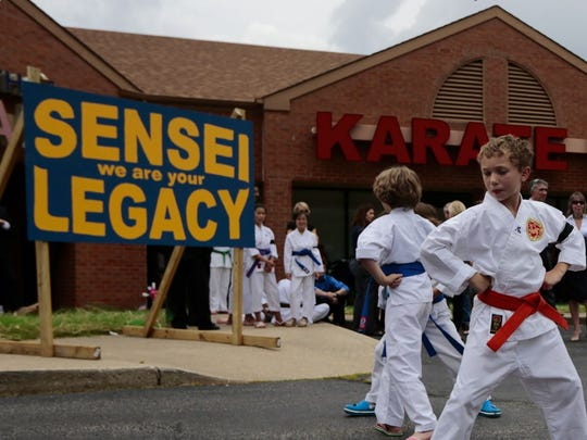 Students run through training exercises as they await the arrival of their fallen sensei, Sonny Kim, in front of their dojo in Loveland.