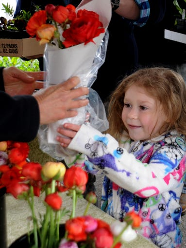 Elona Condron 5, of Asheville,  takes delight in fresh cut roses her mother buys for her at the booth of Full Sun Farm, based in  Big Sandy Mush,  during the opening of the North Asheville Tailgate Market Saturday at UNC-Asheville. The event is a part of GreenFest at UNCA which included the GeenFest Day of Service  in which volunteers  planted gardens  and did  landscaping at 525 Broadway near the Reed Creek Greenway site. John Coutlakis 4-5-14