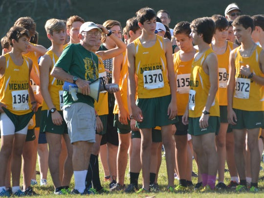 Menard coach Wally Smith (green shirt) meets with his boys cross country team and oversees the 2014 Menard Invitational cross country meet at Fort Buhlow Recreational Area.