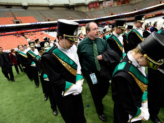 Dan Miller, the assistant director, gets members of the band into formation as they walk back onto the field to hear the results.
