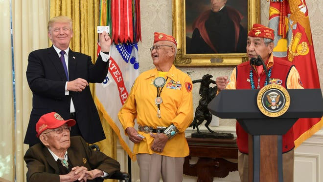 President Donald Trump, standing left, holds up the card of Navajo Code Talker Thomas Begay, center, during their meeting in the Oval Office of the White House in Washington, Monday, Nov. 27, 2017.