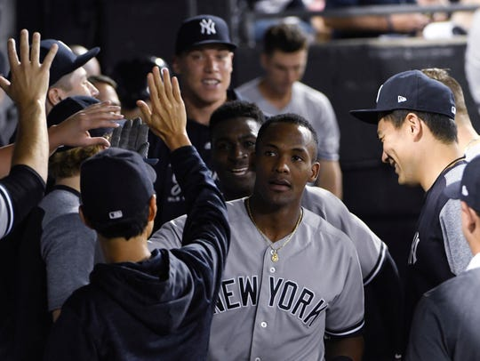 New York Yankees' Miguel Andujar, center, is greeted