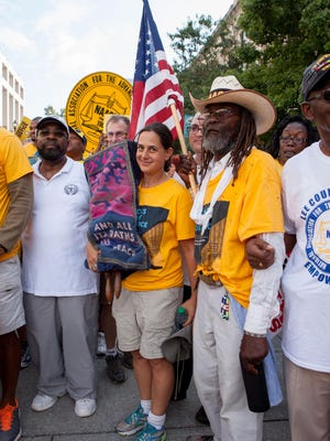 Rabbi Shoshana Leis, of Fort Collins, holds the Torah in Raleigh, North Carolina. To her left is Middle Passage, a Colorado man marching the entire march from Selma to Washington, D.C.