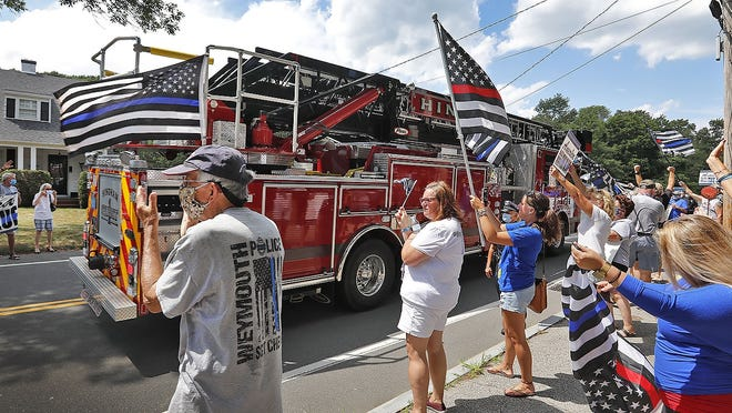 """A Hingham fire truck flying the """"blue lineÓ flag passes police supporters on Central Street.   Supporters of local police line the street in from of the Hingham Police station on Tuesday July 28, 2020 Greg Derr/The Patriot Ledger"""