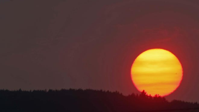 A blood orange sun sets behind the hills of West Salem on a very hot Thursday, Aug. 16, 2012.