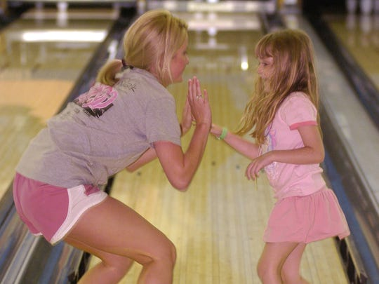 Caroline Frierson (left) and Kaylie Waldman, 5, celebrate hitting the pins while bowling with fellow campers of the 2007 Jambalaya Jubilee.