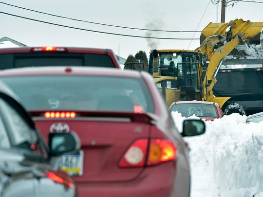 Cars wait as snow is being removed Tuesday, Jan. 26, 2016 on Progress Road, Chambersburg.