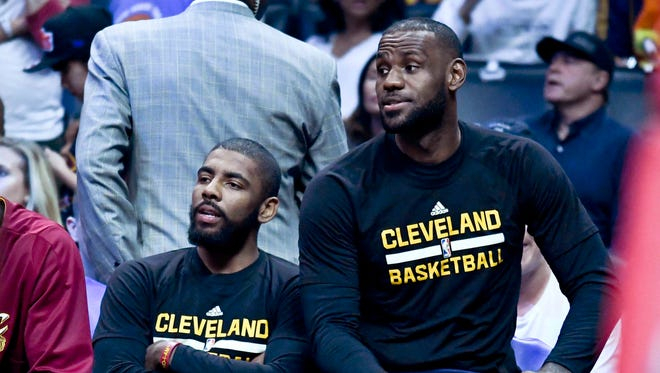Cleveland Cavaliers guard Kyrie Irving and forward LeBron James on the bench during the first half of a NBA game against the LA Clippers at the Staples Center.