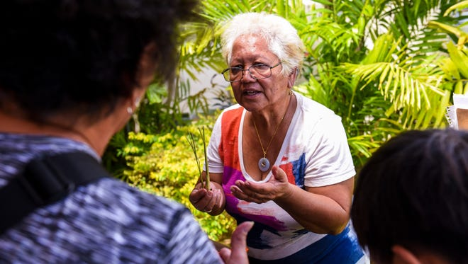 Saina Bernice Nelson, Åmot Farm traditional healer and educator, shares her knowledge of the medicinal benefits of lemongrass stalks with participants during the Ha'ånen Familia event at the Guam Museum on Saturday, April 14, 2018.
