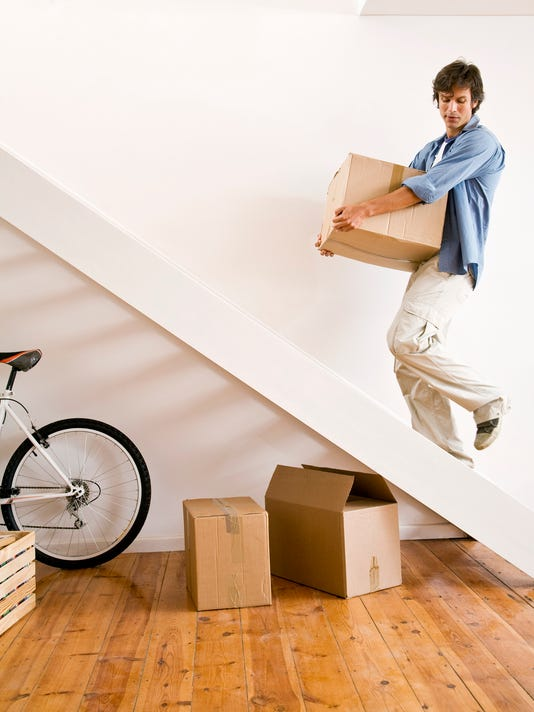 Man carrying moving box up stairs