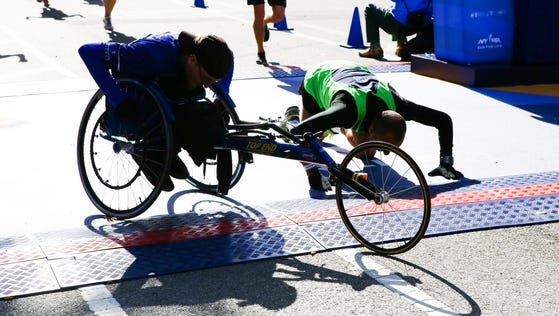 A member of the Achilles Freedom Team from Achilles International crosses the finish line at the New York City Marathon on Nov. 2.