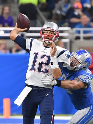 Patriots' Tom Brady throws under pressure from Lions' Anthony Zettel in the second quarter.