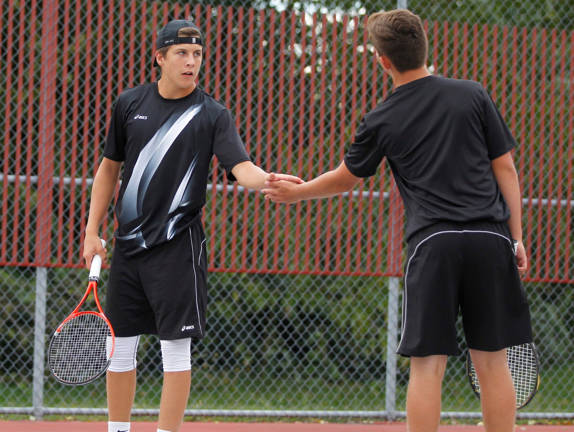 Lafayette Jeff's Danny Isbell, left, and Jacob Isbell celebrate a point against West Lafayette's Jatin Sinahal and Danial Watanabe at No. 2 doubles in the boys tennis sectional championship Friday, October 2, 2015, at Cumberland Courts in West Lafayette.
