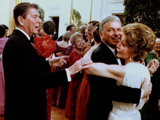 FILE--President Ronald Reagan cuts-in on a dance between Frank Sinatra and Nancy Reagan in this Feb. 6, 1981, file photo. NY126