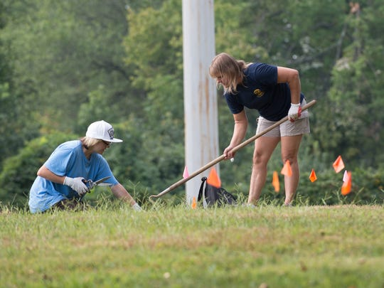 Ashton Jenkot, left and Jessica Jenkot, of Pike Creek, help clean up the grave stones at the Delaware SPCA Stanton Shelter pet cemetery.