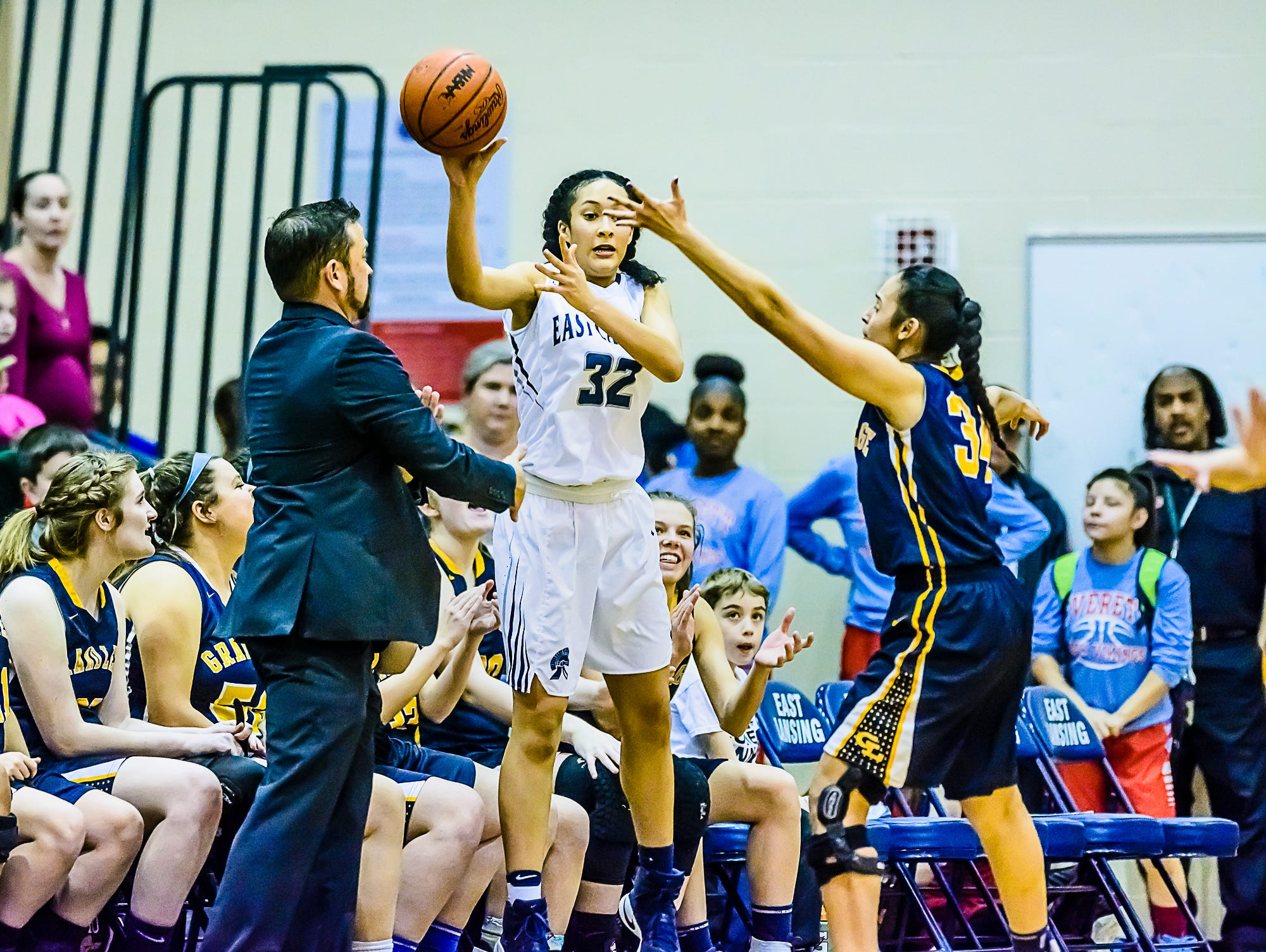 Jade Ayers ,right, of Grand Ledge pressures Aaliyah Nye ,32, of East Lansing as she inbounds the ball in front of the Grand Ledge bench in the last minute of their district semifinal and Grand Ledge trailing by 10 Wednesday March 1, 2017 at East Lansing High School. KEVIN W. FOWLER PHOTO