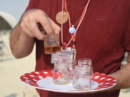 "A member of the Kentucky Fried Camp hands out free bourbon to Burning Man 2017 participants as part of the camp's ongoing ""gifting"" of both bourbon and fried bologna sandwiches."