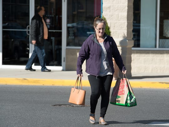 A shopper carries her bags to her car at Tanger Outlets