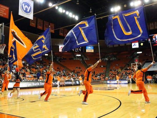The UTEP cheerleaders lead the Miners men's basketball team onto the floor Friday night.